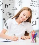 Kleines Studentenmädchen, das in der Schule zeichnet Stockbilder