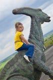 Kleines tapferes Mädchen auf einem Dinosaurier in einem Park Stockfotos