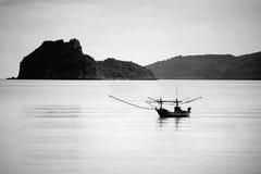 Kleines traditionelles Fischerboot allein auf dem Meer in der Schwarzweiss-Bildart Stockfotos
