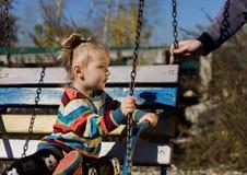 Kleines trauriges Mädchen auf einem Schwingen im Park lizenzfreies stockfoto