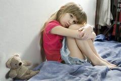 Kleines trauriges Mädchen, das auf dem Bett sitzt Lizenzfreie Stockfotografie
