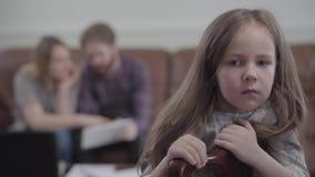 Kleines unglückliches Mädchen des Porträts auf dem Stuhl, der in der Kamera und im Schreien schaut Unscharfe Zahl der jungen Frau stock video footage
