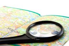 Kleines Vergrößerungsglas auf dem Kartenhintergrund Stockbilder