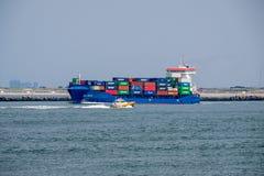 Kleines Versuchsboot führt seetüchtiges Containerschiff stockfotos