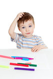 Kleines verwirrtes Kind mit Farbenfeder Stockbilder