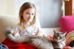 Kleines Vorschülermädchen in den Pyjamas und in ihrer Katze Stockfotografie