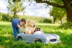 Kleines Vorschulkindermädchen, das großes Spielzeugauto fährt und Spaß mit dem Spielen mit großem Plüschspielzeug bea hat lizenzfreies stockfoto