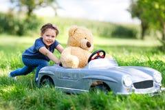 Kleines Vorschulkindermädchen, das großes Spielzeugauto fährt und Spaß mit dem Spielen mit großem Plüschspielzeugbären hat lizenzfreie stockbilder