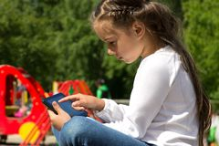 Kleines Vorschulmädchen mit einer Tablette in den Händen, den Tablettenschirm aufmerksam betrachtend Stockfotos