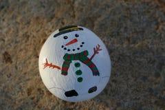 Kleines Weiß gemalter Felsen mit Schneemann stockfotos