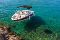 Kleines weißes Boot, das in nahes Ufer des Trinkwassers schwimmt lizenzfreie stockbilder