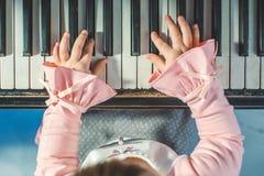 kleines weißes Mädchen, welches das Klavier spielt stockbild