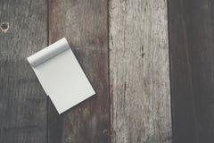 Kleines weißes Notizbuch auf alter Schmutzholzbeschaffenheit lizenzfreies stockfoto