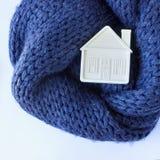 Kleines weißes Spielzeughaus liegt auf einem warmen gemütlichen Schal Konzept-Insel Lizenzfreies Stockfoto