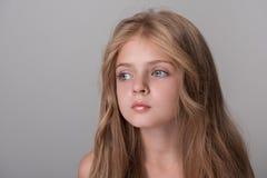 Kleines weibliches Kind wirft mit Pensiveness auf stockfotografie