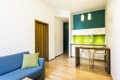 Kleines Wohnzimmer mit grüner Kochnische stockbild
