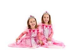 Kleines Zwillingsmädchen wird als Prinzessin im Rosa gekleidet Stockfoto