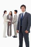 Kleinhandelaar met collega's achter hem Stock Foto