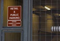 Kleinhandels en openbaar parkerenteken naast een staalomheining royalty-vrije stock foto