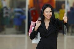 Kleinhandels, gebaar en verkoopconcept - de glimlachende vrouw met vele het winkelen zakken het tonen beduimelt omhoog stock fotografie