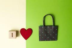 Kleinhandels, verkoop, houd van ik het winkelen, concept met kleurrijke zak, rood hart en houten blok tegen groen gele achtergron royalty-vrije stock foto's