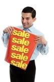 Kleinhandels verkoper die een banner van het verkoopteken houdt stock foto