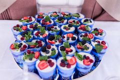kleinigheid Heel wat kleinigheden of cake in blauwe die glazen met bessen worden verfraaid Feestelijk gelaagd dessert in glas royalty-vrije stock afbeeldingen