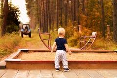 Kleinkind auf einem Kinderspielplatz, der unscharfen Traktor betrachtet Herbstton Lizenzfreies Stockbild