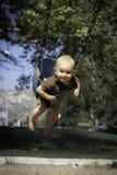 Kleinkind auf einem Schwingen Stockbild