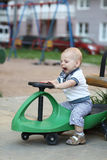 Kleinkind auf Spielzeugauto Stockbild