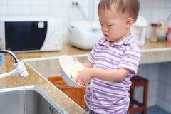 Kleinkind-Babykind des Asiaten 2-Jähriges, das den Spaß tut die Teller/wäscht Teller in der Küche steht und hat Stockfotos