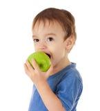 Kleinkind bitting den grünen getrennten Apfel Lizenzfreie Stockfotografie