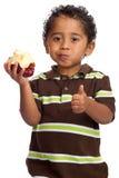 Kleinkind, das Apple isst und Daumen aufgibt Stockfoto
