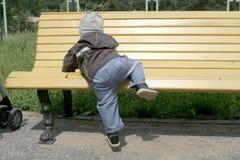 Kleinkind, das auf Bank steigt Stockfotografie
