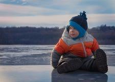 Kleinkind, das auf gefrorenem See sitzt Stockfotos