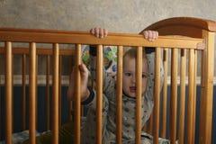 Kleinkind, das aus Krippe heraus steigt Stockbild