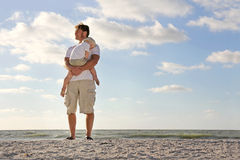 Kleinkind, das in den Armen des Vaters auf Strand durch Ozean stillsteht lizenzfreies stockfoto