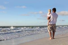 Kleinkind, das in den Armen des Vaters auf Strand durch Ozean stillsteht stockfotos