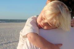Kleinkind, das in den Armen des Vaters auf Strand schläft lizenzfreies stockbild