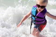 Kleinkind, das in den Meereswogen in der Schwimmweste spielt Lizenzfreie Stockfotos