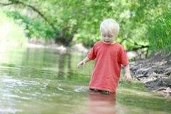 Kleinkind, das draußen im Fluss spielt Stockfotografie