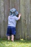 Kleinkind, das durch Zaun späht Lizenzfreie Stockfotos