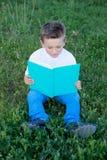 Kleinkind, das ein Buch an der Außenseite liest Lizenzfreies Stockbild