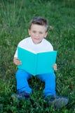 Kleinkind, das ein Buch an der Außenseite liest Lizenzfreie Stockfotos