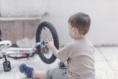Kleinkind, das ein Fahrrad repariert Lizenzfreie Stockbilder