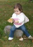 Kleinkind, das ein großes Blatt anhält, das sie fand Lizenzfreie Stockfotografie