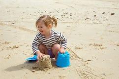 Kleinkind, das ein Sandschloß aufbaut Stockfotos