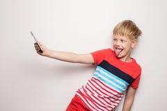 Kleinkind, das ein selfie mit dem Handy lokalisiert auf wei?em Hintergrund nimmt Sie hat Angst lizenzfreie stockfotografie
