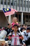 Kleinkind, das eine malaysische Flagge wellenartig bewegt Lizenzfreies Stockfoto