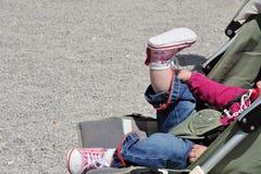 Kleinkind, das in einem Spaziergänger sitzt Lizenzfreie Stockfotos